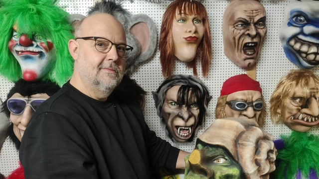 Mann vor Wand mit Masken