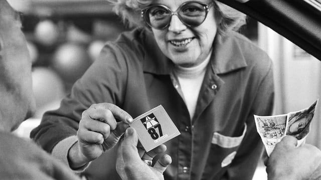 Eine Frau verkauft einem Autofahrer eine Autobahnvignette 87 für 30 Schweizer Franken.