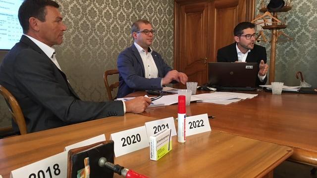 Drei Männer sitzen am Tisch, darauf Schraubzwinge, Kopfehmittel und roter Filzstift