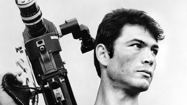Nahaufnahme von Robert Foster in schwarz weiss mit Kamera auf der Schulter.