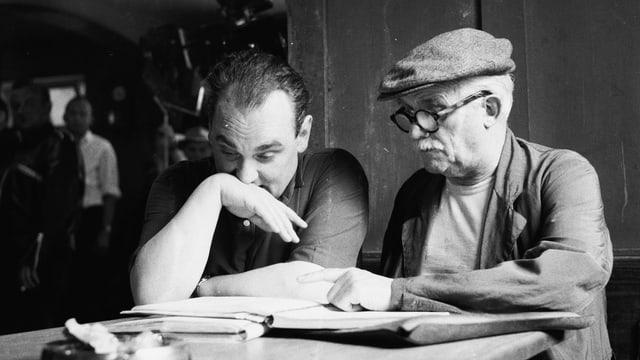 Zwei Männer sitzen an einem Tisch und sehen sich ein Dokument an.