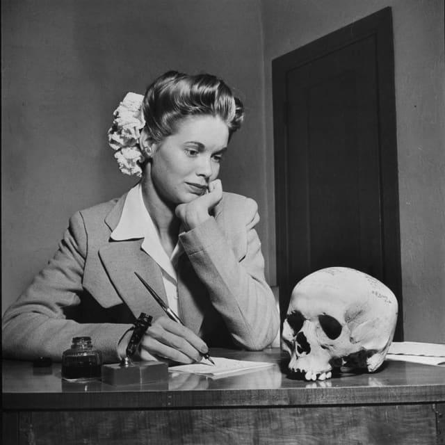 Eine Frau sitzt am Schreibtisch und schaut auf einen Totenkopf.