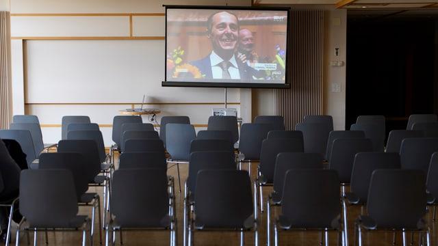 Leere Stuhlreihen vor einem grossen Bildschirm mit dem gewählten Bundesrat Ignazio Cassis.