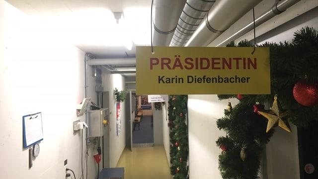 Ein langer Gang in einem Zivilschutzbunker. Im Vordergrund ein gelbes Schild mit der Aufschrift: Präsidentin. Karin Diefenbacher.