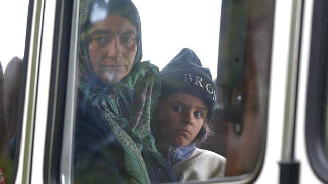 Eine Frau mit Kopftuch und ein Kind mit Strickmütze hinter einer Scheibe eines Buses.