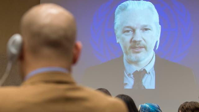 Julian Assange auf einer Leinwand – im Vordergrund der Rücken eines Mannes.