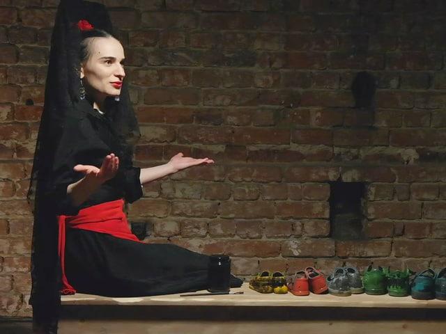Eine rumänische Schauspierin sitzt auf einem Tisch, hat verschiedene Paare Schuhe vor sich und hält die Hände offen.