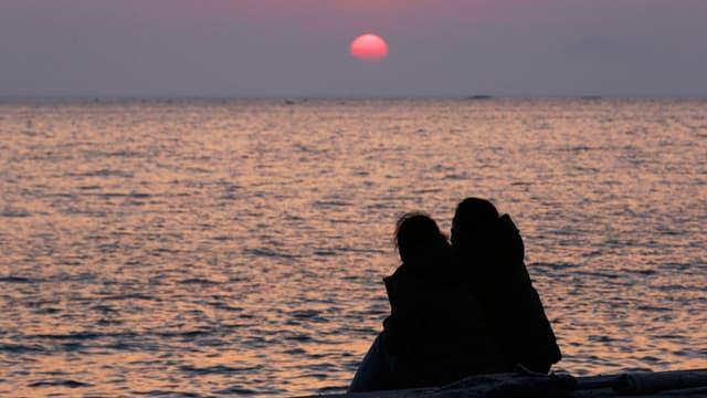 Zwei Leute sitzen am Ufer und schauen den Horizont mit der untergehenden Sonne an.