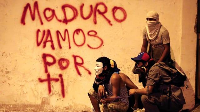 Vermummte Demonstranten vor einer Wand, auf der auf Spanisch sinngemäss steht: «Maduro, wir kriegen dich.»