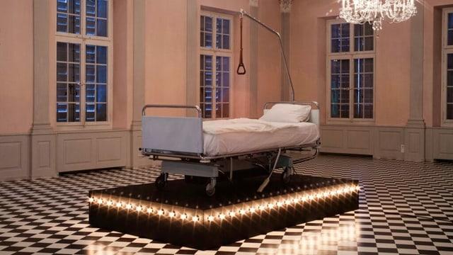 Ein Spitalbett auf einem Sockel mit Lichtern in einem Saal mit Kronleuchtern.