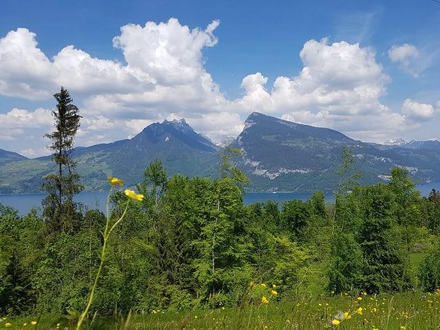 Quellwolken über den Berggipfeln, darunter liegt ein See.