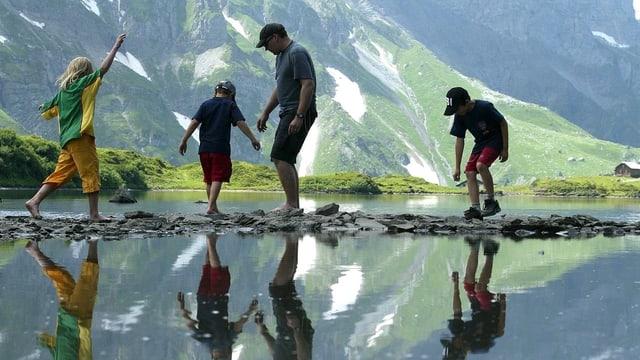 Vater mit drei Kindern an einem See