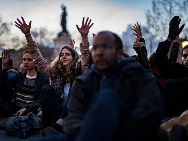 Personen die Hände in die Luft haltend.