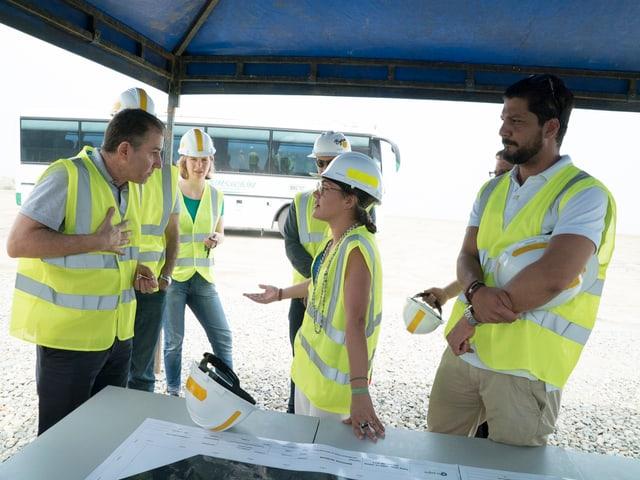 Fünf Personen in gelben Warnwesten diskutieren miteinander.
