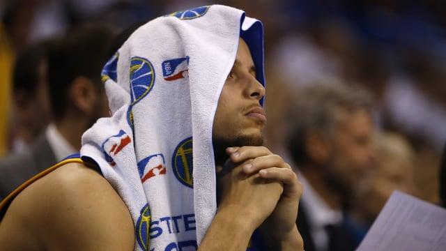 Stephen Curry sitzt mit einem Handtuch über dem Kopf am Spielfeldrand.