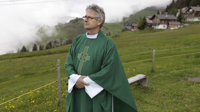 Ein Pfarrer steht auf einer Wiese
