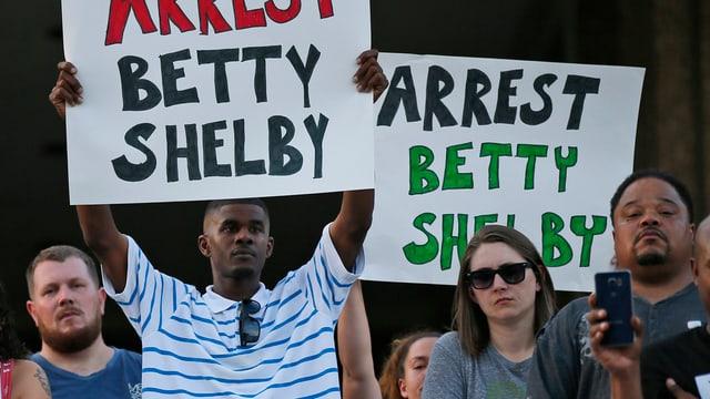 Protestas a Tulsa suenter ch'in afroamerican era vegnì sajettà giu entras ina policista. Plirs demonstrants tegnan enta maun placats cun si: Arrest Betty Shelby
