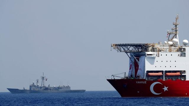 Bohrschiff mit türkischem Emblem im Vordergrund, dahinter ein Kriegsschiff.