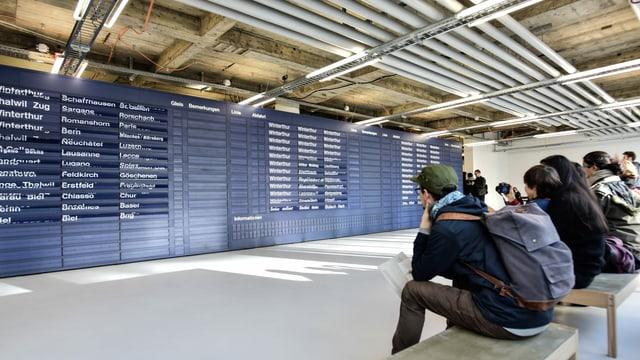 Besucherinnen und Besucher betrachten im MuDA die ausrangiert Fallblattanzeige des Zürcher Hauptbahnhofs