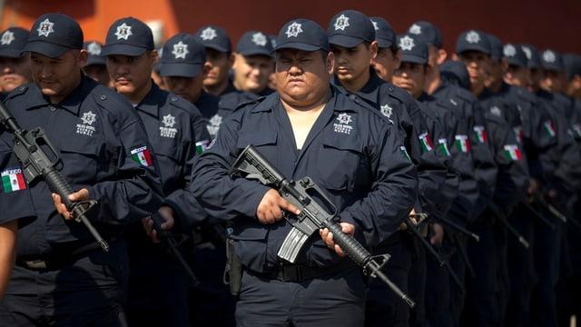 Sicherheitleute in einer Reihe stehend mit einem Maschinengewehr.