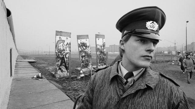 Eine Schwarz-Weiss Aufnahme eines Polizisten, mit Überresten der Berliner Mauer
