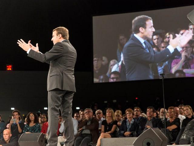 Emmanuel Macron spricht an einer Veranstaltung in die Menge.