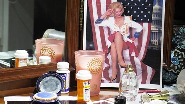 Fotos, Medikamente und eine Puderdose auf einem Schminktisch.