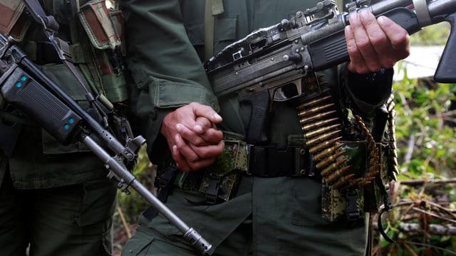 Zwei Gewehre und Hände von zwei Menschen, die sich umklammern