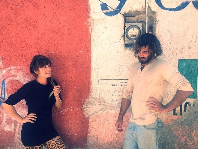 eine schöne Frau und ein bärtiger Mann vor roter Hauswand