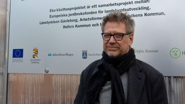 """Ein Mann mit Brille steht vor einer Tafel mit der Aufschrift """"Eko Växthusprojektet"""""""