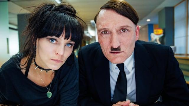 Zwei Schauspieler schauen in Kamera, darunter ein Adolf-Hitler-Darsteller.