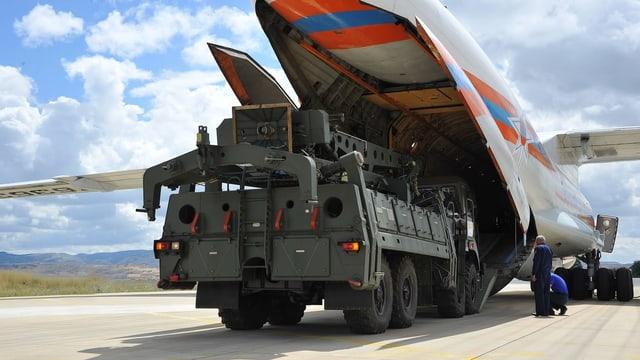 Ein Militärfahrzeug verlässt den Bauch eines Transportflugzeugs.
