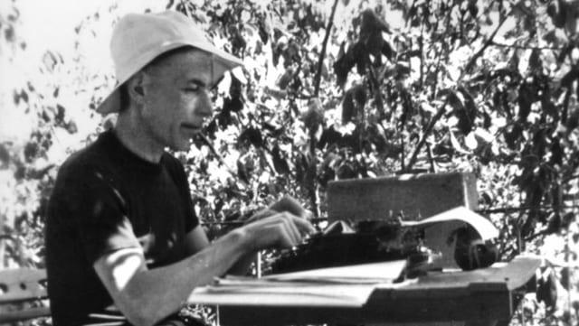 Mann mit Hut im Garten an der Schreibmaschiene