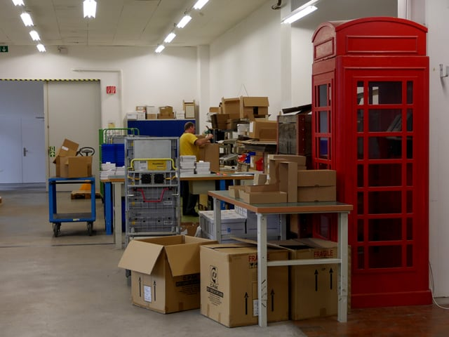 """In der Abteilung """"Post"""" der Sozialfirma gadPLUS AG in Biel stehen viele Kartonschachteln herum. Auffallend ist eine rote Telefonkabine, wie man sie aus England kennt. Sie steht inmitten des Schachtelbergs."""