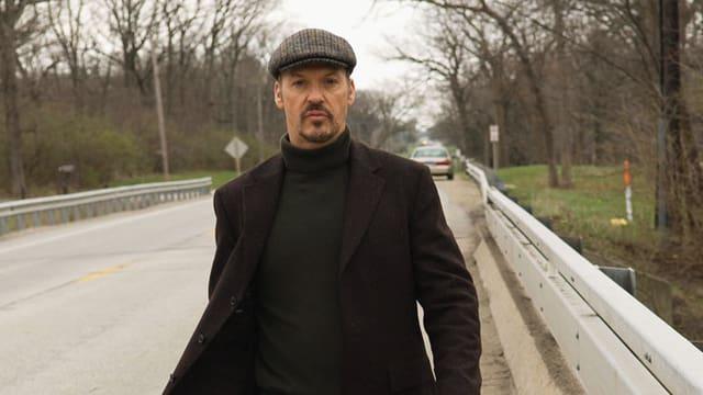Ein schwarz gekleideter Mann geht einer Strasse entlang.