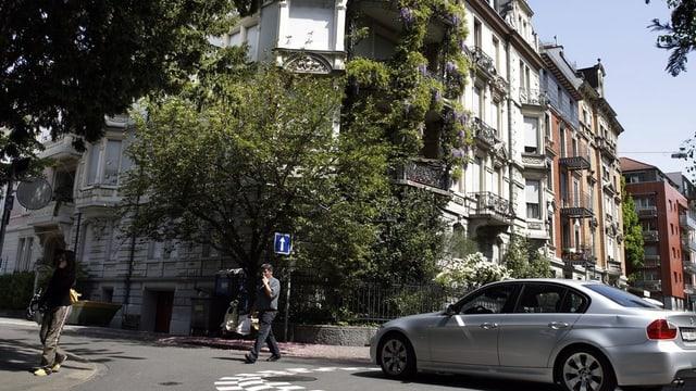 Fassaden von Häusern, davor eine Quartierstrasse mit einem Kreisel.