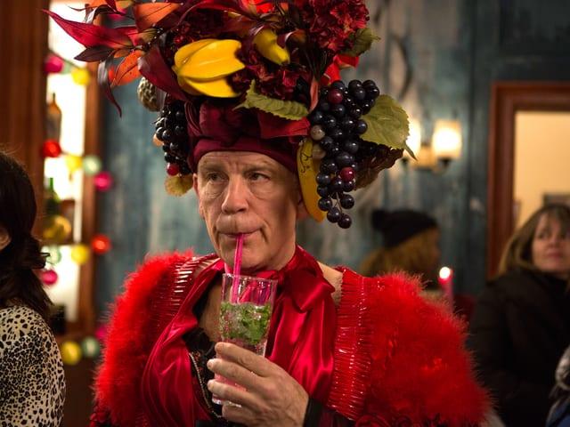 Mann nippt an einem Drink, auf seinem Kopf ein Hut aus künstlichen Früchten.