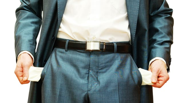 Ein Mann im Anzug hat nichts in seinem Hosentaschen.