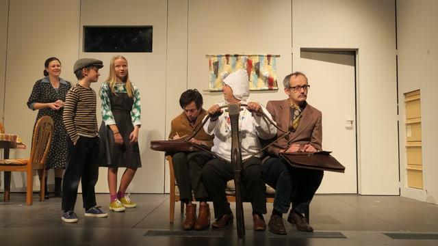 Szene in einem Landtheater: Links stehen zwei Kinder auf der Bühne, im Vordergrund sitzen drei Männer. Einer ist als Wilhelm Tell verkleidet und hält eine Armbrust.