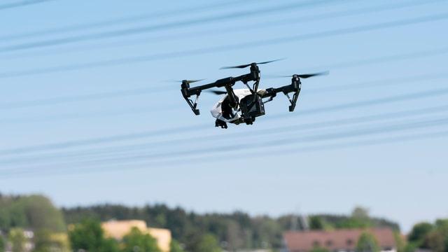 Eine Drohne fliegt in der Luft über einem ländlichen Gebiet.