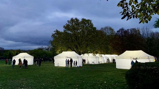 Leuchtende weisse Zelte mit Personen davor, die auf ihren Coronatest warten, sind in der Dämmerung zu sehen.