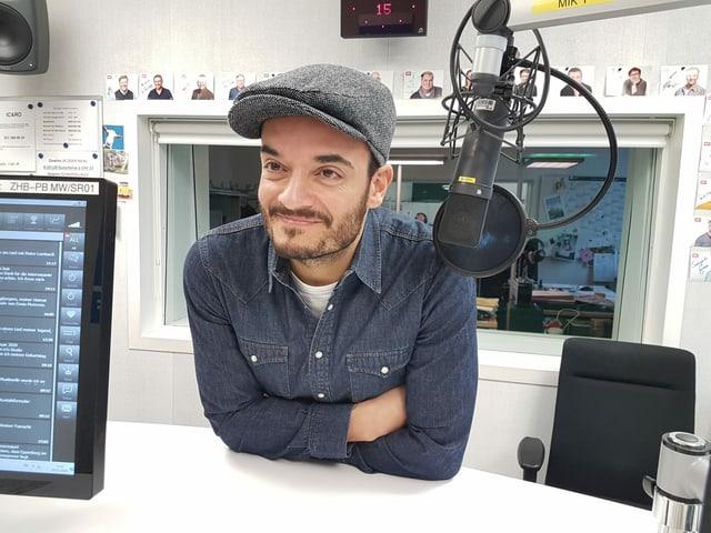 Mann lehnt sich über Sendepult im Radiostudio.