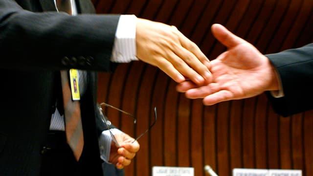 Die Hände zweier Anzugträger bewegen sich zum Händeschütteln aufeinander zu.