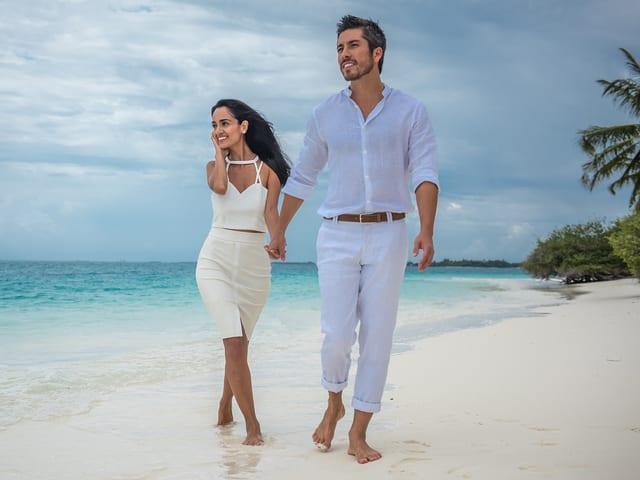 Moderator Max Loong und seine Ehefrau Sepideh beim Spaziergang am Strand.