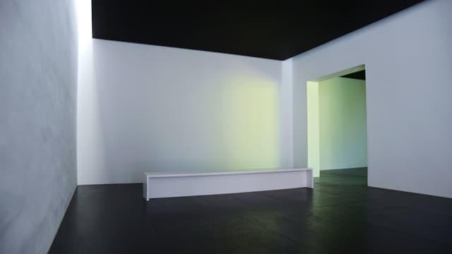 Leerer Raum mit schwarzer Decke und schwarzem Boden, darin eine weisse Bank.