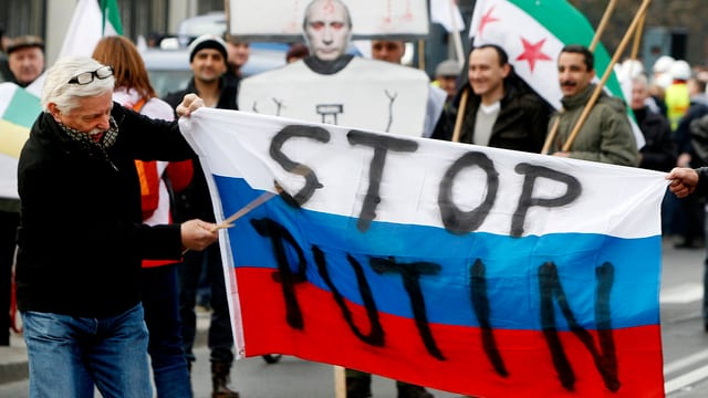 Polnische Demonstranten tragen eine russische Fahne mit der Aufschrift «STOP PUTIN».