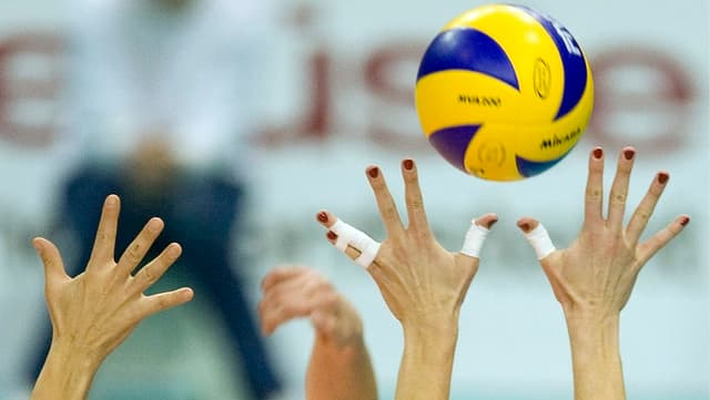 Frauenhände greifen nach einem bunten Ball