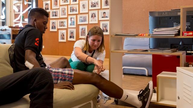 Eine Frau klebt einem jungen Mann ein Pflaster aufs Knie.