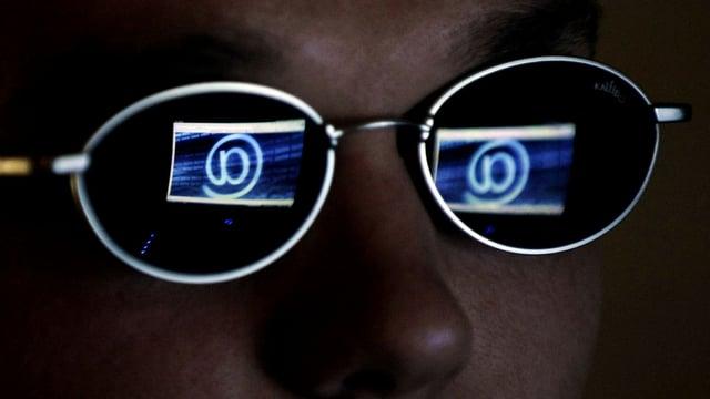 Mann mit Brille, in der Brille spiegeln sich @ Zeichen.