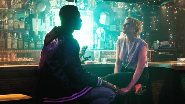 Eine schummrige Bar, eine Frau und ein Mann sitzen sich am Tresen gegenüber und schauen sich in die Augen.